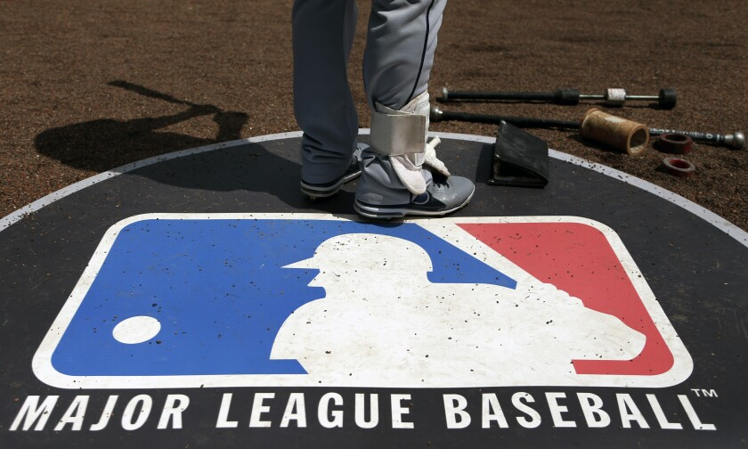 A player stands on the MLB logo during a game.