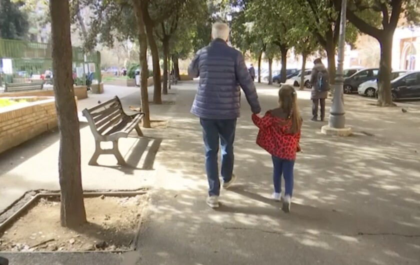 A young girl walk with her elderly grandparent along a tree lined avenue in Rome, Italy, Thursday March 5, 2020, after the Italian government closed all schools to assist in the fight against the COVID-19 virus. Some of the most vulnerable people, grandparents, have been forced to face possible virus infection as they look after young family members in playgrounds and parks in the city.(AP Photo)