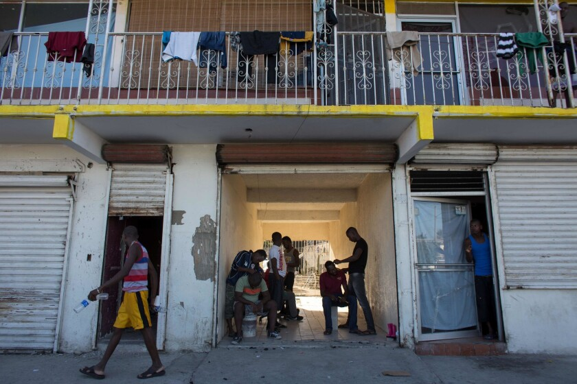Haitian migrants seeking asylum in the United States wait for the opportunity to get a spot in a room at a rented house in the Mexican border city of Tijuana.