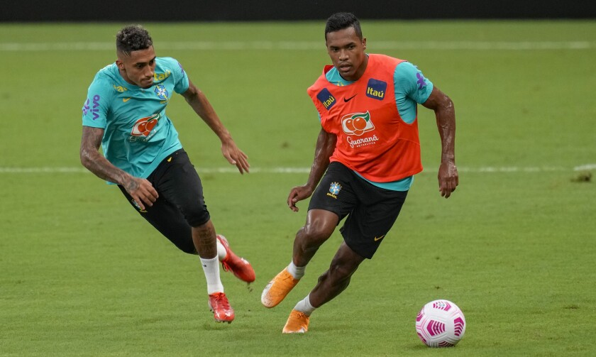 Brazil's Alex Sandro, right, and Raphinha practice during a training session in Manaus, Brazil, Wednesday, Oct. 13, 2021. Brazil will face Uruguay in a qualifying soccer match for the FIFA World Cup Qatar 2022 in Manaus on Thursday. (AP Photo/Andre Penner)