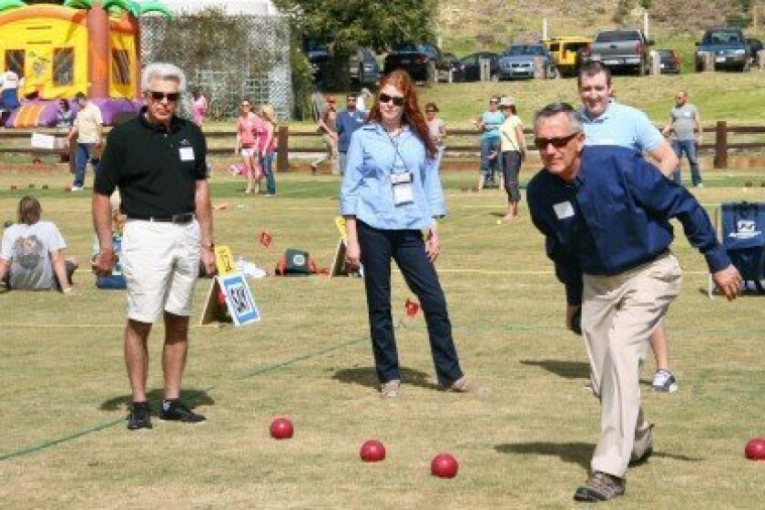 Del Mar Mayor Terry Sinnott bowling in a past Del Mar – Solana Beach Mayors' Competition, with (left to right) Al Corti (Del Mar Councilman), Wendé Protzman (Solana Beach Deputy City Manager), and Dan King (Senior Management Analyst) watching. Other players and children's jump house in the background.