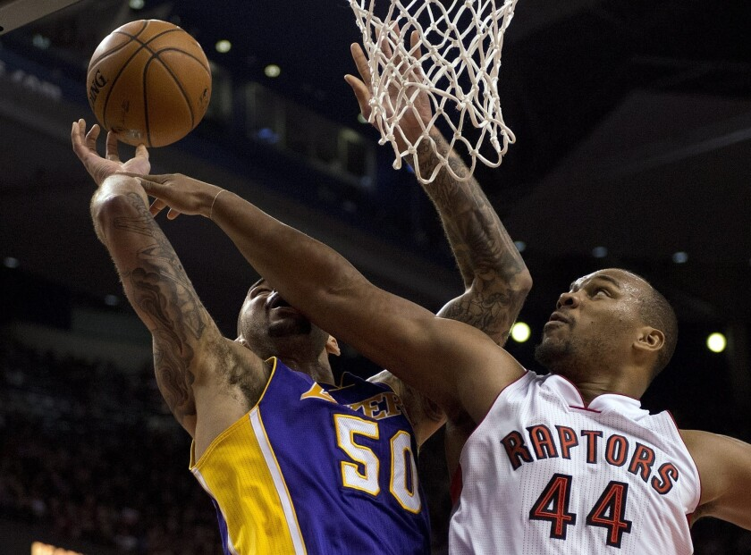 Raptors forward Chuck Hayes blocks the shot of Lakers center Robert Sacre in the first half of a 2014 game.