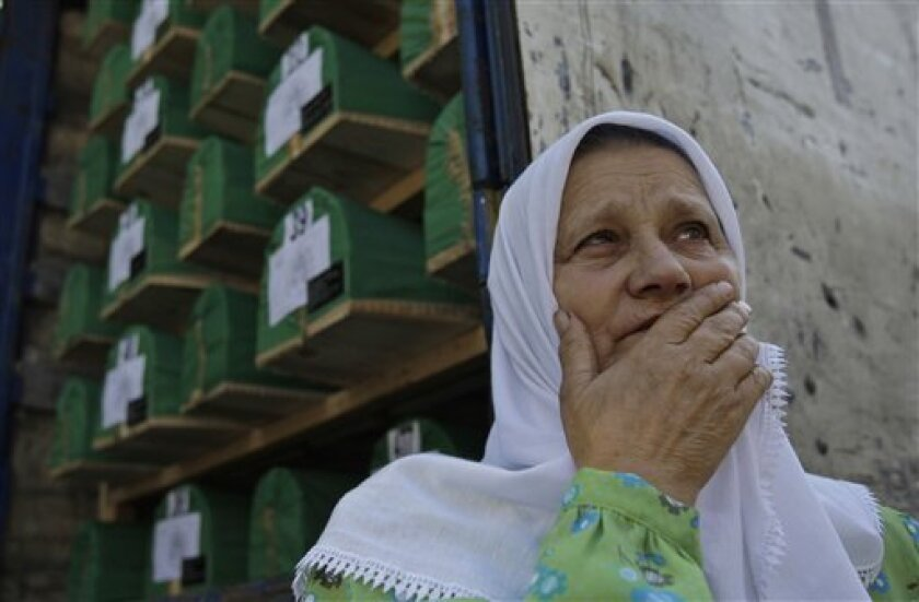 Bosnian Muslim woman Hamida Avdic stands near one of three trucks loaded with caskets during a farewell ceremony for the caskets of 614 Srebrenica massacre victims, near Visoko city morgue, Bosnia on Saturday, July 9, 2011. Bodies were prepared for mass burial ceremony scheduled on July 11, at Potocari Memorial Cemetery in Srebrenica. This year's mass burial, marking the 16th anniversary of the fall of Srebrenica, is organized for 614 bodies, collected from mass grave sites in eastern Bosnia. In previous years, more than 4,500 bodies were buried at Srebrenica Memorial Cemetery, after being excavated from mass graves in eastern-Bosnia and positively identified.(AP Photo/Amel Emric)