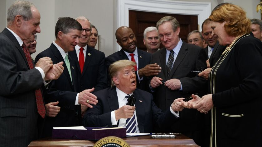 President Trump hands out pens to Sen. Heidi Heitkamp (D-S.D.), right, and other lawmakers after signing legislation rolling back some Dodd-Frank financial regulations at the White House on Thursday.