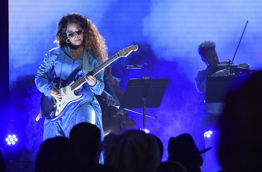 H.E.R., in sunglasses, plays the guitar onstage.
