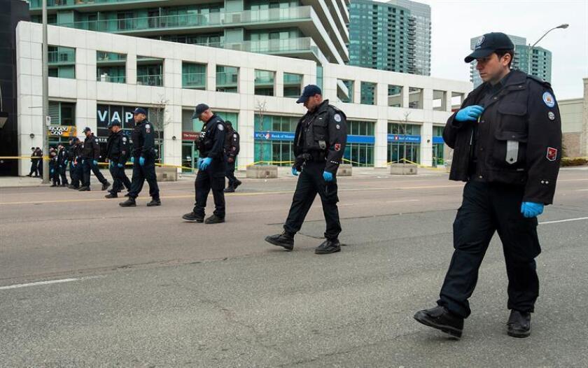 Miembros de la policía de Toronto buscan pruebas en el lugar en el que una furgoneta atropelló el pasado lunes a varias personas en Toronto (Canadá) hoy, 24 de abril de 2018. EFE