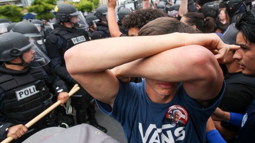 A protester covers his eyes as police try to clear the area after Trump supporters and anti-Trump protesters clashed.
