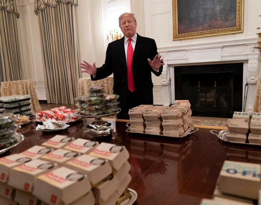 US President Donald J. Trump presents the fast food to be served due to the government shutdown to the Clemson Tigers at the White House in Washington, DC, USA, 14 January 2019. The Clemson Tigers will visit the White House to celebrate their College Football Playoff national championship. EPA-EFE/CHRIS KLEPONIS / POOL