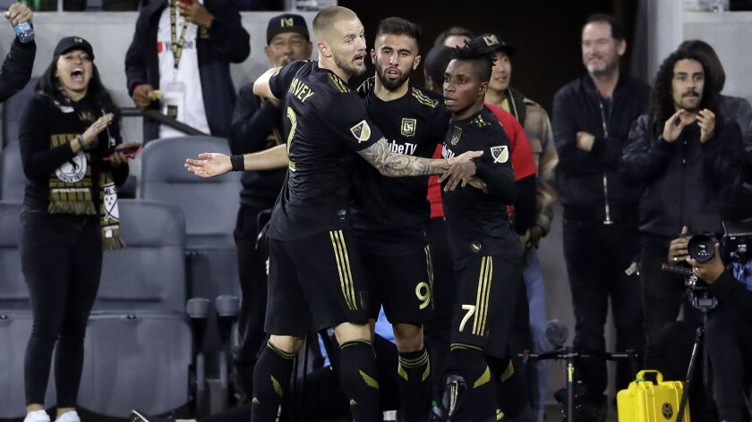 LAFC's Diego Rossi, center, is hugged by teammates Jordan Harvey, left, and Latif Blessing after scoring a goal against Real Salt Lake during the first half of a game March 23, 2019.