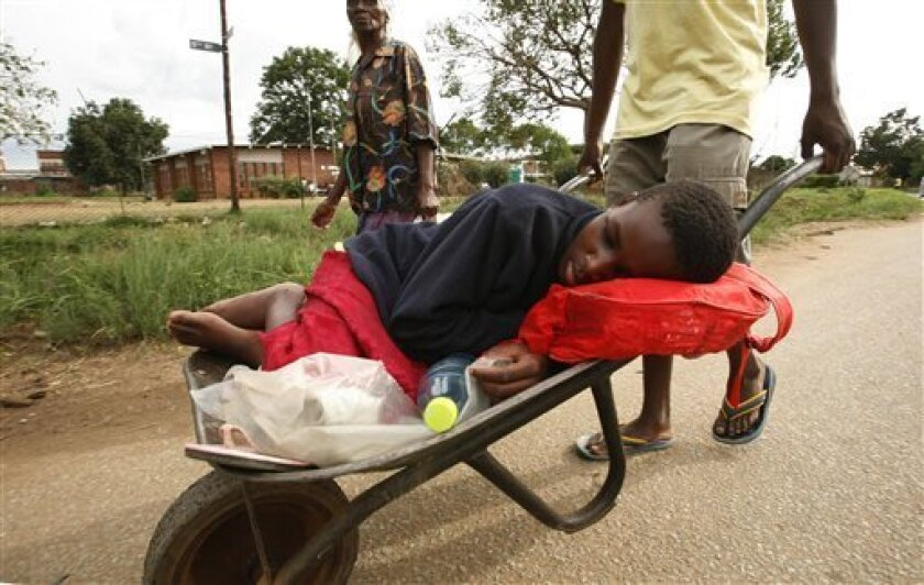 A woman suspected to be suffering from cholera, is transported in a wheelbarrow to a clinic for treatment, in Harare, Thursday, Dec. 11, 2008. President Robert Mugabe said Zimbabwe's cholera crisis was over, even as the United Nations raised the death toll from the disease to 783. (AP Photo)