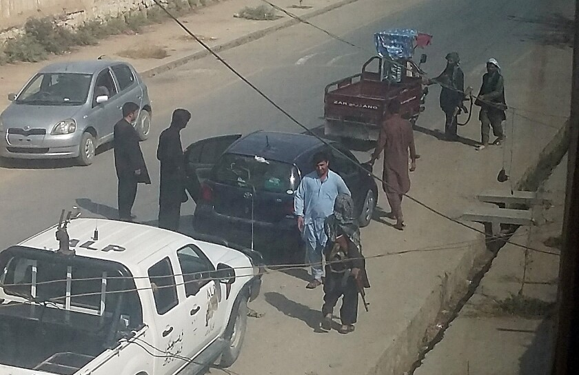 Taliban fighters search passengers and civilian vehicles at a checkpoint in Kunduz on Tuesday. Taliban militants fanned out in full force across the Afghan city they captured the day before.