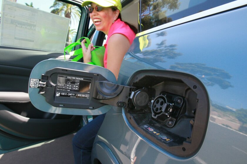 A view of the electric charging connector receptacle of a Mercedes B-Class Electric Drive car. Climbing our of the car is Bianca Andriese.