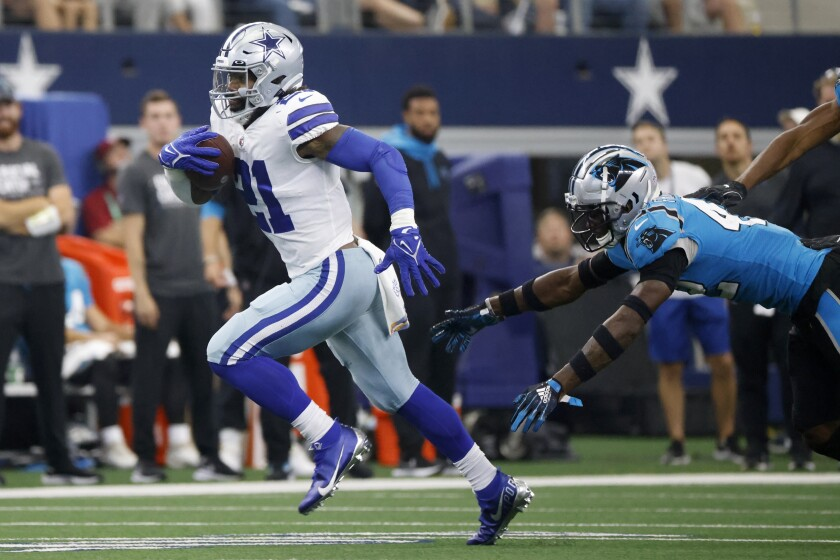 Dallas Cowboys running back Ezekiel Elliott (21) gets past Carolina Panthers safety Sam Franklin (42) for a long gain in the second half of an NFL football game in Arlington, Texas, Sunday, Oct. 3, 2021. (AP Photo/Ron Jenkins)