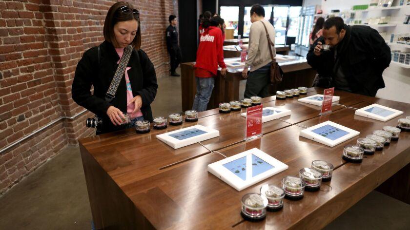 Denise Nugent of Los Angeles looks over flower strains of marijuana at MedMen, a marijuana store in L.A.