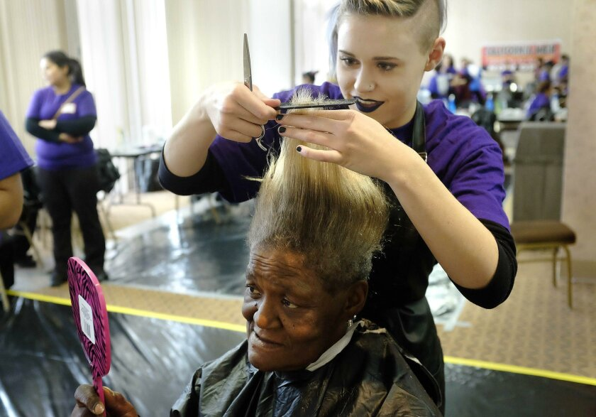 |Sandra Kincade, who has been homeless for four years, looks in the mirror while San Diego City College cosmetology student Cadence Lewis works on her hair Wednesday at Project Homeless Connect.