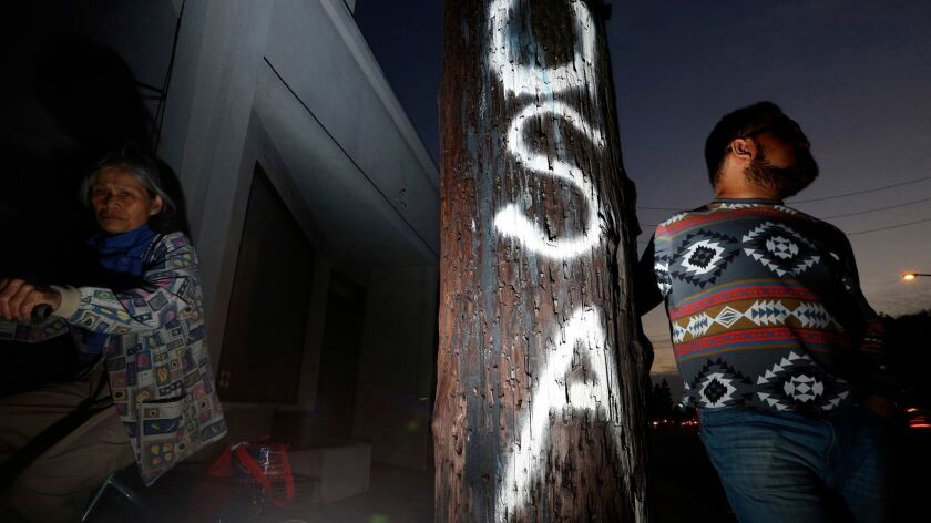 """Seth Hernandez, 24, right, stands next to a pole spray painted with """"USA"""" on it in Culver City on Dec. 7. Hernandez is a member of the sizable Asian community in Los Angeles that is undocumented."""