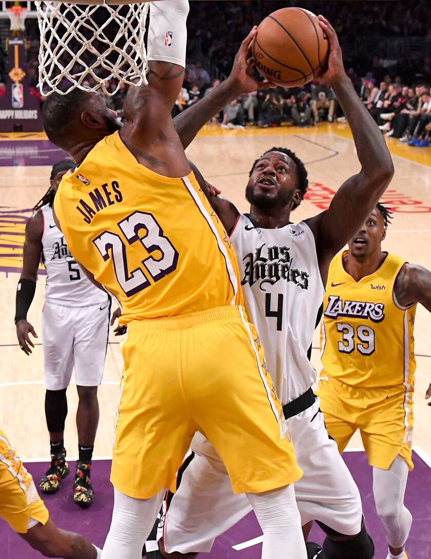 Clippers forward JaMychal Green tries to score inside against Lakers forward LeBron James during the second half of a game Dec. 25, 2019, at Staples Center.