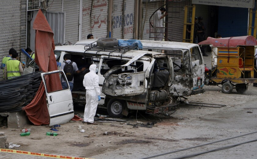 Pakistani investigators examine damaged vehicles at the site of a suicide bombing Wednesday in Lahore.