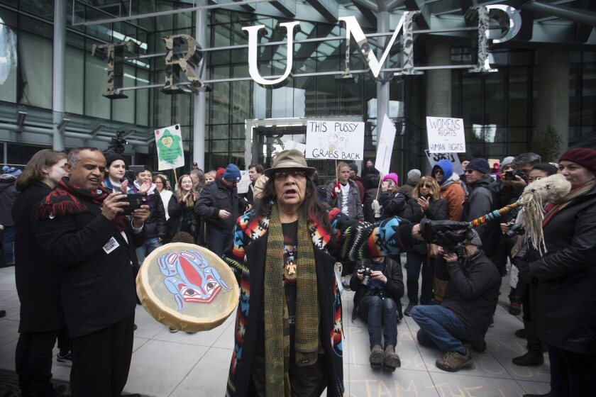 Viviane Sandy of Williams Lake, Canada, plays a drum outside the official opening of the Trump International Hotel & Tower Vancouver on Feb. 28, 2017.
