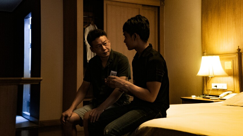 Two men sit on the corner of a bed.
