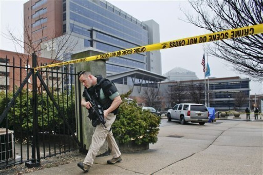 Law enforcement officials makes his way around the perimeter outside the New Castle County Courthouse in Wilmington, Del. on Monday Feb. 11, 2013, after three people died Monday morning in a shooting at a courthouse, including the shooter, authorities said.  (AP Photo/ Joseph Kaczmarek)