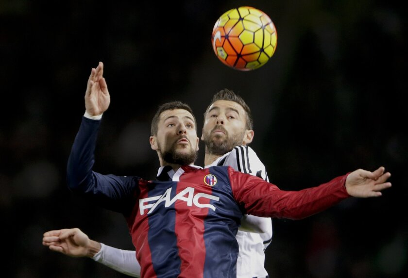 Bologna's Mattia Destro  and Juventus' Andrea Barzagli jump for the ball during their Serie A soccer match at the Dall' Ara stadium in Bologna, Italy, Friday, Feb. 19, 2016. (AP Photo/Antonio Calanni)