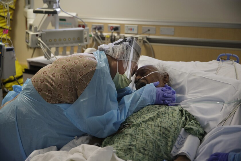 FILE - In this July 31, 2020, file photo, Romelia Navarro, 64, weeps while hugging her husband, Antonio, in his final moments in a COVID-19 unit at St. Jude Medical Center in Fullerton, Calif. In November 2020, California is reaching an unwelcome coronavirus record: its 1 millionth positive test. (AP Photo/Jae C. Hong, File)