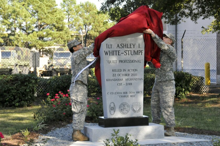 Soldiers with the 230th Brigade Support Battalion, 30th Armored Brigade Combat Team, North Carolina National Guard, unveil a memorial to 1st Lt. Ashley White-Stumpf at the Goldsboro National Guard Armory, N.C., Sept. 15, 2013. Red roses, said to have been White-Stumpf's favorite color and flower, surround the structure. White-Stumpf was serving on a cultural support team when the Army Ranger unit she was deployed with encountered an improvised explosive device in Afghanistan, October 22, 2011. (U.S. Army National Guard photo by Staff Sgt. Kelly S. LeCompte/Released)