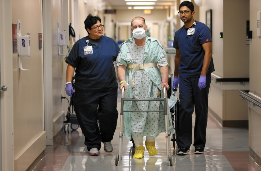 A patient being treated for cancer walks with therapists at a hospital in Houston, Texas. The share of callers connected with insurance after contacting the National Cancer Information Center has increased under the Affordable Care Act.