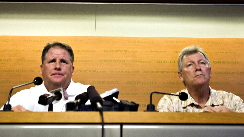 Oregon football head coach Chip Kelly, left, and athletic director Mike Bellotti hold a news confere