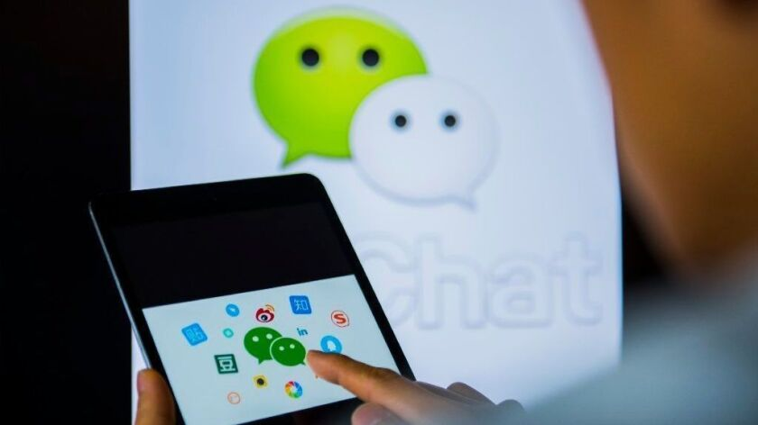 Young man holds a smart device while using WeChat app