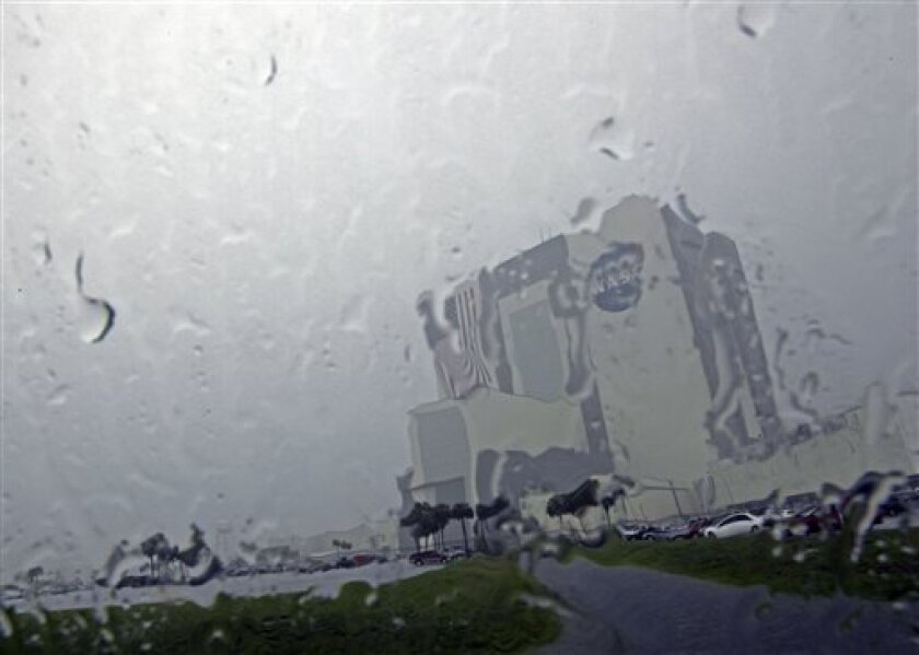 The Vehicle Assembly Building is seen through a window during a downpour at the Kennedy Space Center Thursday, July 7, 2011, in Cape Canaveral, Fla. The space shuttle Atlantis is scheduled to launch on Friday, July 8 and is the 135th and final space shuttle launch for NASA. (AP Photo/David J. Phill