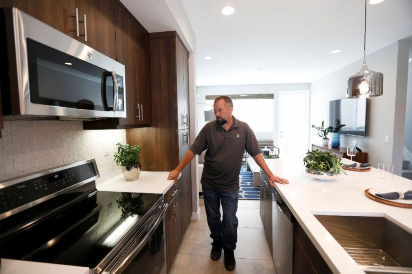 Construction manager Chris Smith shows off an induction cooktop at an all-electric, solar-powered townhome development being built by City Ventures in Bellflower, on March 25.