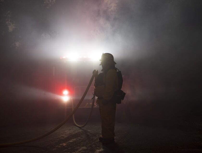 A firefighter holds a hose amid the Carmel fire near Carmel Valley, Aug. 18, 2020.