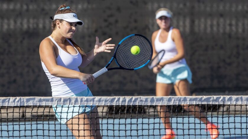 Corona del Mar's Bella McKinney, left, returns a shot during a doubles match with her partner Shaya