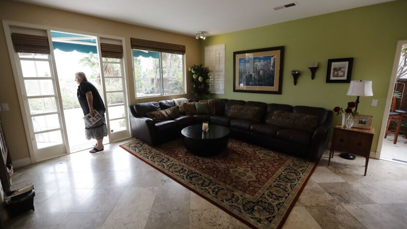 In this Oct. 3, 2018 image, Vicky Campbell looks around a home for sale in her former neighborhood d