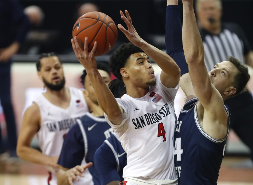 San Diego State's Trey Pulliam scores against Utah State's Justin Bean in the Mountain West Conference tournament final.