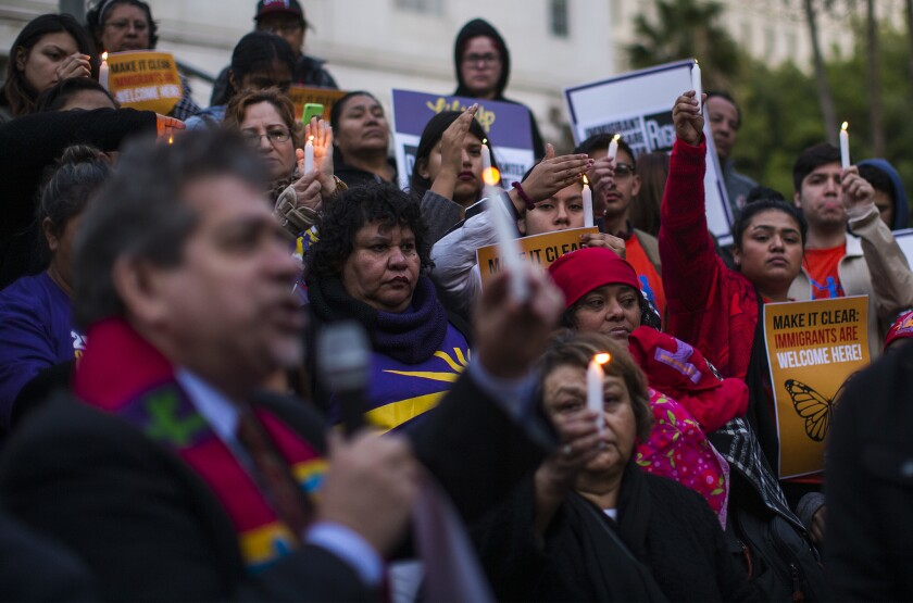 Protesters raise their candles in unison during a vigil against President Donald Trump's executive orders on immigration at City Hall in Los Angeles on Wednesday.