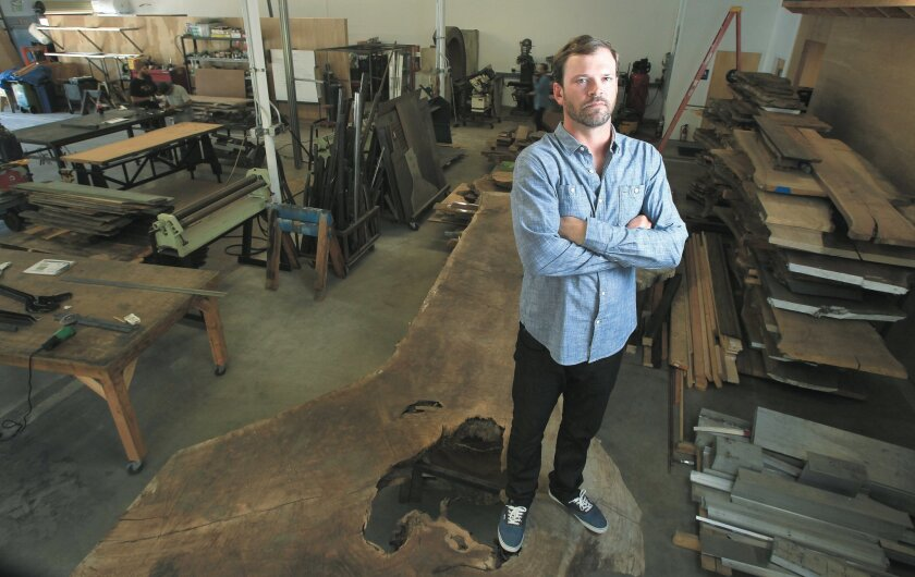 Todd Noe, owner of Noe Design Co., stands on single piece of walnut, cut from a fallen tree in the Los Angeles area, in his studio in Sorrento Valley.