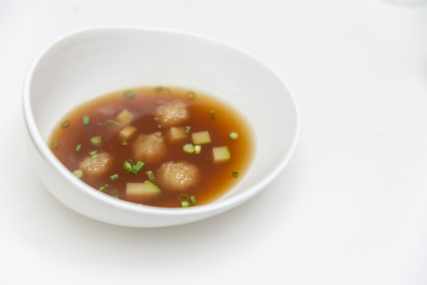Potato dumpling soup with potato and zucchini in light broth served with seasoning sauce