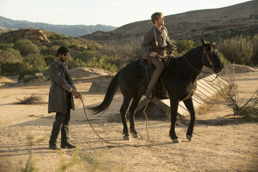 Logan (Ben Barnes) is tied up by William (Jimmi Simpson).