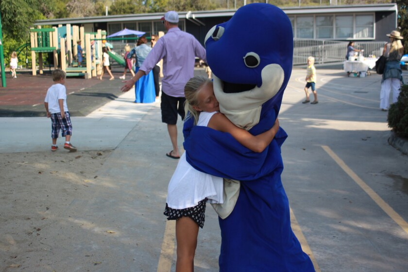 Spout the Whale from La Jolla Elementary School greets a student.