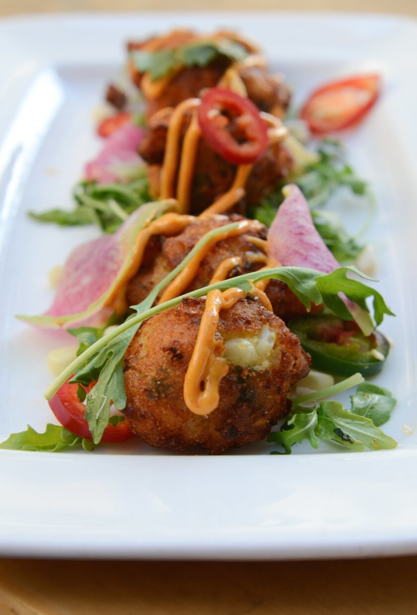 Shrimp & Roasted Corn Fritters, small fried cakes stuffed with pieces of Baja white shrimp and corn, decorated with jalapeño rings, arugula, shaved radish and harissa aioli.