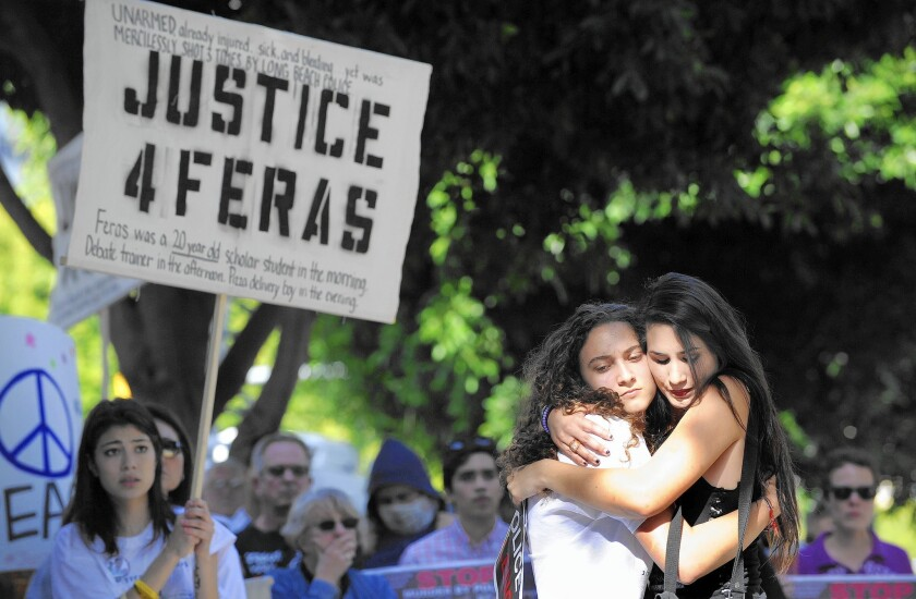 At a demonstration in Long Beach over the shooting death of Feras Morad, his sister, Ghada Morad, 16, second from right, is hugged by Sonia Hernandez, whose brother was killed by Anaheim police in 2012.