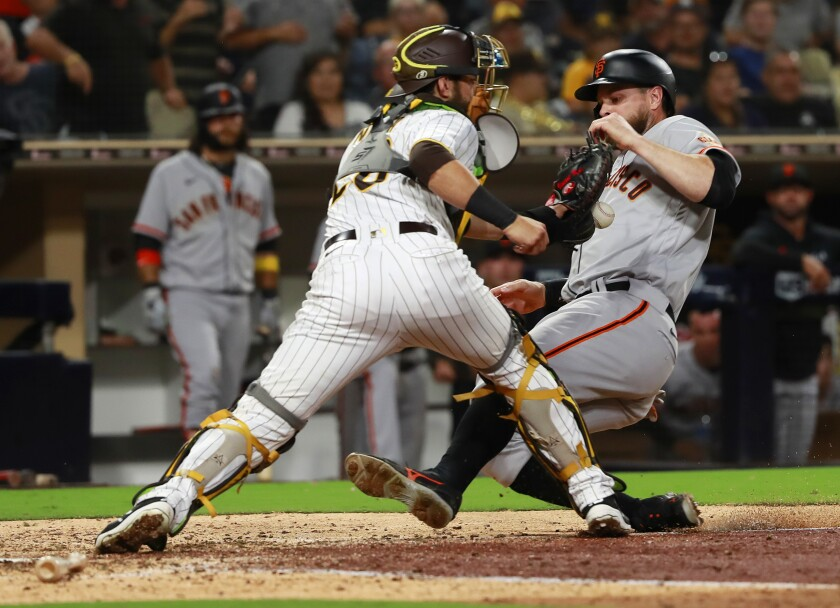 Padres catcher Austin Nola can't complete the tag as the San Francisco Giants' Brandon Belt scores