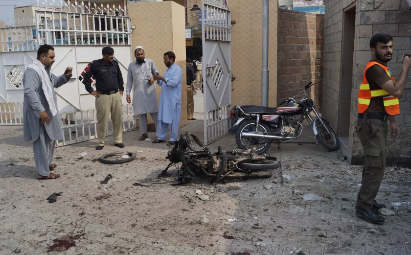Pakistani officials examine the site of a bombing