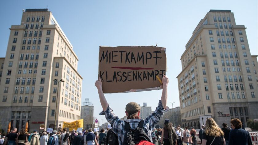 """A protester holds up a sign that says """"Rent Fight, Class Fight"""" at a demonstration against rising apartment rents in Berlin."""