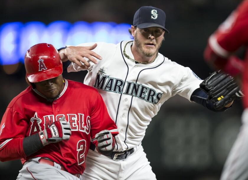 Mark Lowe (d) de los Mariners choca con Erick Aybar de Angels, en la primera base.