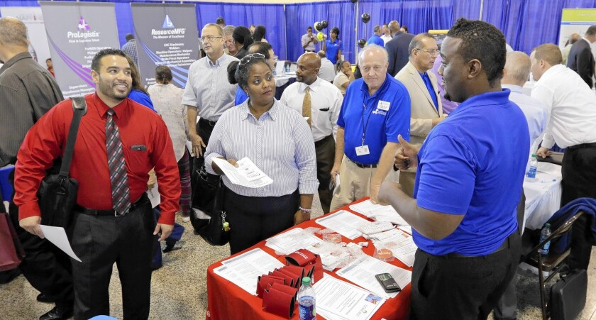 Job seekers attend a hiring fair for veterans in Fort Lauderdale, Fla. Although the U.S. economy this year recovered all of the jobs lost during the recession, the new jobs are largely in lower-wage industries such as hospitality and healthcare, a new analysis says.