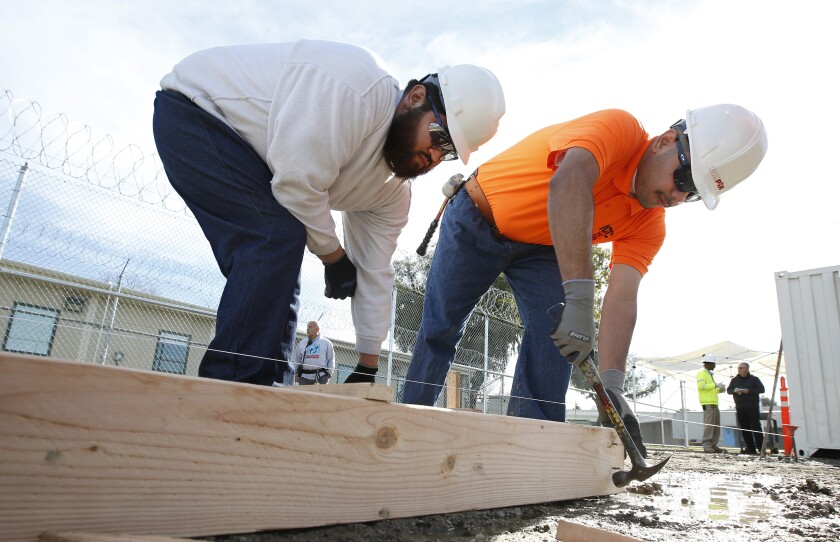 Two young men in hard hats work with lumber on construction site